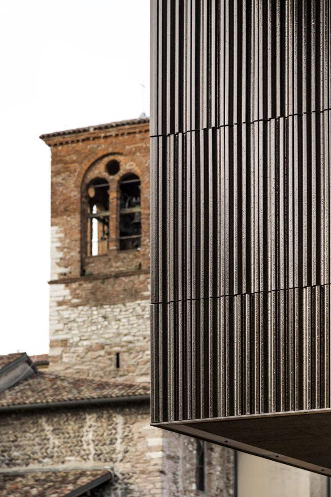 Fassaden-Gegenüberstellung der neuen Pflegeeinrichtung in Nembro mit der Kirche San Nicola im Hintergrund